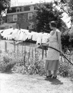 The vintage housewife watering lawn or garden with clothes hung outside on clothes line