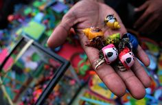 Balikpapan, Indonesia: A local market trader offers crabs with painted shells for sale