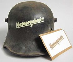 WW2 Messerschmitt Factory Guard, Air Defence & Fireman's Helmet Stencil Messerschmitt AG was a famous German aircraft manufacturing corporation (AG) named after its chief designer, Willy Messerschmitt, and known primarily for its World War II fighter aircraft, notably the Bf 109 and Me 262. This stencil marking would have been worn on the helmets of Messerschmitt employed personnel, air defence, Fire units and Security guards.   www.WarHats.com