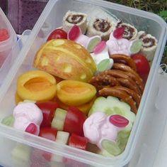 Bentobox mit Tomaten-Gurken-Spießchen, Aprikosenhälften, Gurkenblumen, Salzbrezeln, Apfelkäferchen, Nutellaröllchen und Grünohrhasen. Dazu noch eine Schale mit Wassermelonenblumen.