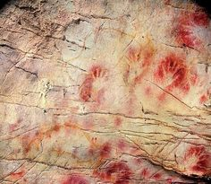 """This undated photo provided shows detail of the """"Panel of Hands"""" inside a cave known as El Castillo in Spain. The painting shows red disks and hand stencils made by blowing or spitting paint onto the wall. By measuring the decay of uranium atoms, scientists have determined the painting is older than 40,800 years, making it the oldest known cave art in Europe."""