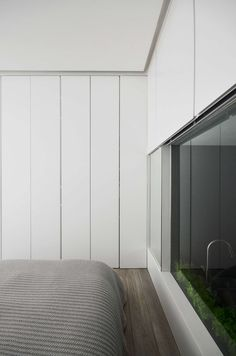 In this bedroom, walls of white cabinets travel from the floor to the ceiling. There's also a window into the kitchen, that can be covered for privacy.