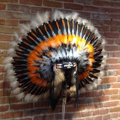 This Thunderbird Headdress is a reproduction of a Native American artifact. It was created and made by two Navajo artists, Linda Lee and Betsy Piaso, including intricate beadwork and painted feathers