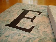Monogram on canvas using scrapbook paper, printed letter and modge podge.