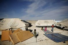 Syrian refugee children stand amid materials that will be used to protect their living quarters in Za'atri refugee camp ©UNHCR/B.Sokol