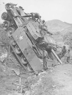 """""""June 1951 a British Mk III Centurion tank, painted with US markings runs off the road north of Seoul. A difficult recovery job for the men of the Royal Electrical and Mechanical Engineers. The Centurion's 20-pdr gun (the most powerful tank gun used in Korea) was renowned for its accuracy in destroying enemy bunkers, but never met the T-34 in combat in Korea. Note the failed HE penetrations on the side skirts."""""""