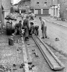 M4 Sherman tank crew doing some track maintenance. Strong possibility that the commander is the guy with a clean uniform just standing there.