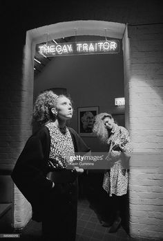 Two young women at the entrance to The Gay Traitor cocktail bar at The Hacienda nightclub, Manchester, 1983. The bar takes its name from Sir Anthony Blunt, a British art historian and Soviet spy. A portrait of Blunt hangs on the wall of the bar (centre).