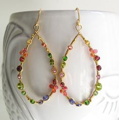.........golden teardrops dotted with colorful gemstones..... Made to order with a two week turnaround. Minor differences. Never exact, but always gorgeous. 18 gauge 14k gold filled wire lengths have been forged into teardrop hoop earrings. Studded with orange sapphire, chrome