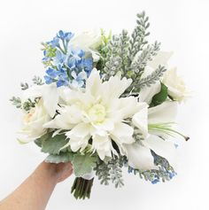 A large posy of oriental lilies, pale peach classic roses, blue lilac, santolina and dusty miller.
