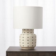 Shop Grid Black and White Polka Dot Table Lamp. Simple black blocks get into formation atop white earthenware base. Formed by hand on a potter's wheel using locally-sourced clay, table lamp is glazed, fired, and finished by hand. White linen shade diffuses a soft light. CB2 exclusive.