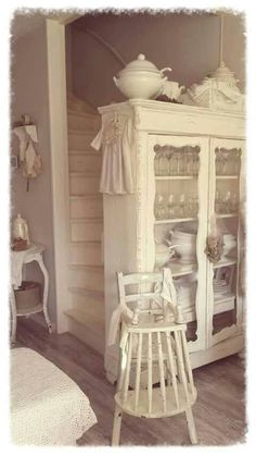 Love the idea of a vintage curio cabinet at the end wall at bottom of stairs