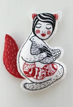Embroidered Soft girl totem by Nadya Sheremet  Nadya Sheremet is an embroidery artist located in Russia (from Ukraine). She was inspired by little trinkets from the pre-war period, and also by the mountainous landscapes surrounding her. Her pieces are very graphic in nature and feel like precious toys.