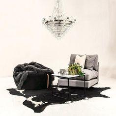 Grå Valen fåtölj. Koskinn, marmorbord, marmor, bord, soffbord, svart, vit, metall, Baggen pall, fotpall, sammet, päls, pläd, fusk, filt, kristallkrona, vardagsrum, möbler, inredning.