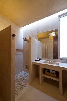 reforma baño rústico de obra con acabado microcemento, zona de ducha separada con tabiques a media altura. presupuestON.com