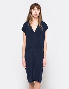 From 6397, a lightweight flowy oversized dress in Navy.  Features deep v-neckline, capped sleeves, waistline, silky interior, below-the-knee length and oversized fit.  •Lightweight oversized dress in Navy •Deep v-neckline •Capped sleeves •Waistli