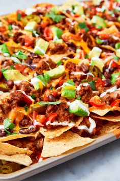 Is there anything more satisfying than a loaded tray of nachos, still hot from the oven? Here's how to make nachos (with our favorite insanely easy recipe), including how to make it healthy, the best toppings, and what kind of cheese to use on them. Mexican Food Recipes, Beef Recipes, Cooking Recipes, Ethnic Recipes, Mexican Dishes, Nacho Recipes, Recipies, Mexican Entrees, Taco Salad Recipes