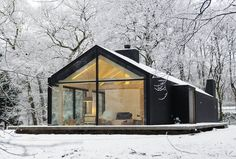 Oisterwijk Brouwhuis was designed by Bedaux de Brouwer Architecten and its finished structure resembles an elongated barn in the forests of Oisterwijk. The pitched roof makes way for a window wall that covers one entire end of cabin. The exterior is clad in black-stained wood, which matches the wooded forest and contrasts with the snow.