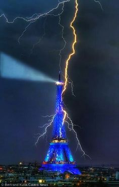 The Eiffel Tower is lit up in blue as it is hit by a lightning bolt that zig-zags across the Parisian sky