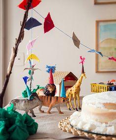 """Festa de um ano feita em casa. A bicharada chega com chapéu de festa e se instala na mesa do bolo; gravetos sustentam bandeirinhas de linho e as casinhas, ao fundo, foram feitas com """"caixa de torrada sem glúten virada do avesso"""", conta a mãe, Elisa, que fez toda a decoração (Foto: Cacá Bratke/Editora Globo)"""