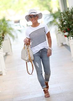 Fashionable summer travel look with simple statement tee and jeans. Add a necklace to elevate the look. Summer fashion over 40 | 40 Plus summer fashion | Summer outfit ideas #HatsForWomenSporty