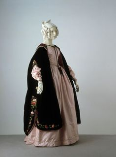 "1838-1842 British Dress and mantle at the Victoria and Albert Museum, London - From the curators' comments: ""The dress is worn with a velvet mantle, appliquéd and embroidered with flowers. Loose mantles, cloaks and capes were popular forms of outer coverings during this period. When skirts are very full, they are easier to wear than tightly fitting coats and jackets."""