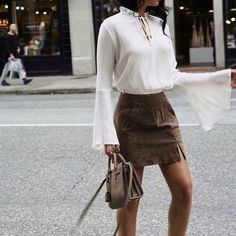 white peasant top with bell sleeves and tan mini skirt.