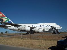 """A Boeing 747SP, a shortened Boeing 747-100, is parked at an fenced-off airport, facing right. The aircraft's engines feature prominently, as a mobile stairway is placed next to one of its doors under the """"N"""" in South African."""