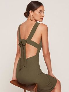 Where do you think you're going? This is a tight fitting, midi length dress with an open back and a back bow detail.
