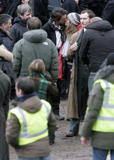 """Stealing a kiss from the producer: star Robert Downey Jr. and producer (and his wife) Susan Downey smooch on the set of """"Sherlock Holmes"""" (Jude Law is to the right)."""
