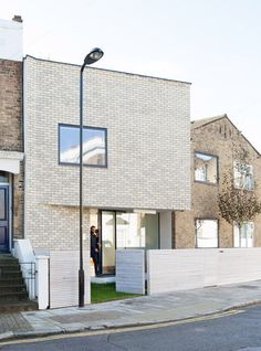 The upper storey of this brick extension to a mid-century home in north London projects over the entrance to form a porch.
