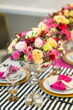 Black and white striped tablecloth paired with gold plates and colorful florals.