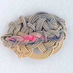 カゴ編み作家のYOSHIKOさんの籐で編んだカゴアクセサリーです。 変幻自在に籐を扱うYOSHIKOさんのアクセサリーは 見たことのないユニークなデザインで大人気です。 小さなアートを身につけている気分になれます。 このコームも水引のように籐を編んで、 さらに三つ編みにしたものを染めています。 こんなことできるのはYOSHIKOさんしかいません。 裏にコームが縫い止めてあります。 結び目をボンドで補強してあります。