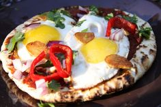 I made this easy egg breakfast pizza last week when I was on vacation. It is a great meal and such an easy breakfast recipe idea that it can be made almost anywhere. I used a pita for the base, if you prefer, use another type of flatbread or a tortilla. You will need: Pita Egg Tomato Paste Sriracha Sauce Red Pepper Red Onion Cilantro Garlic The first thing you want to do is to cup up the garlic into fine slices. Then brown it in a pan with butter and set aside.   Then, chop up the pepper…