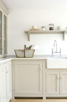 Gorgeous gray-beige and white remodeled Shaker-style kitchen with a white porcelain drop-in basin sink, shiny silver hardware, glazed ceramic knobs on the recessed panel Shaker cabinets below, and glass front cabinets above, open shelving above the sink, and a vintage flower basket to boot.