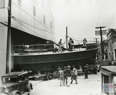 Men look on as U.S. Army Boat BBP 395 is pulled out of the factory in Louisiana and onto the street in the 1940s, Higgins Industries. From The Digital Collections of the National WWII Museum. 2008.280.011.