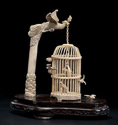 Chinese carved and inked ivory birdcage on 20th century wooden stand.