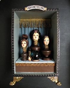THREE HEADS ARE BETTER THAN ONE This box was inspired by the mechanical fortune telling booths found in penny arcades in the early 20C. They often had life sized, rather sinister figures sitting in a booth dispensing fortunes, marvellous! This is a wooden box with an assemblage of vintage doll parts and antique wooden finials, antique bullion braid, with an antique glass globe sitting centrally. Also using silks, faux jewels, and paper. The box sits on four beautifully carved brass feet. ...