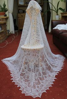 """Classic lace patterns used to create a simple, elegant Shetland Lace shawl. Knitting begins with the scalloped lace edging and works in towards the centre. Designed for 7 x 15g skeins (or 5 x 25g balls) of J&S Shetland 1 ply cobweb wool. Finished size 50"""" square."""