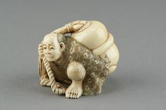 Japanese ivory carved Netsuke, Edo period, signed on side, featuring man carrying a large bottle. H: 5 cm, W: 6 cm, 93 grams.
