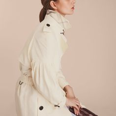 An oversize Burberry trench coat cut from Italian silk for a light, fluid drape, complemented by a simple hook-and-eye closure and D-ring belt. Sleeves are gently puffed for added dimension.