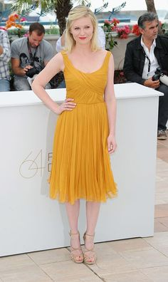 """Kirsten looked lovely at the """"Melancholia"""" Photocall at the Cannes Film Festival in this saffron Chloe chiffon dress."""