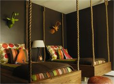 chocolate brown green orange boy's bedroom design with chocolate brown walls, twin swing beds, green & orange faux deer heads, orange pink brown red green pink polka dot striped pillows striped bedding, orange leather pouf and tripod lamp. Suspended Bed, Toddler And Baby Room, Hanging Beds, Hanging Rope, Hanging Chairs, Diy Hanging, Floating Bed, Boys Bedroom Decor, Safari Bedroom