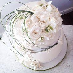 Hochzeitstorte mit Rosen, Orchideen und Gräsern