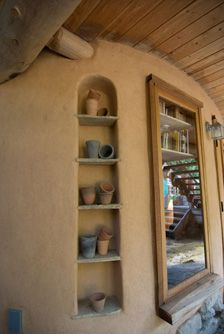 nice shelving idea -- I <3 cob houses!! Could do this instead of top kitchen cabinets for plates, bowls, glasses. Have sturdy twigs hanging out to hang mugs on. Maybe a mug tree :)