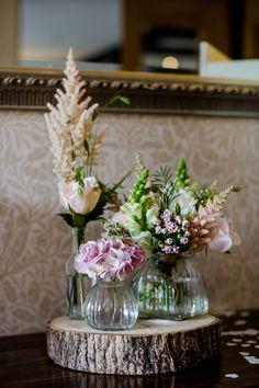 Log slice, vintage bottles with pretty flowers.