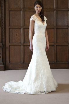 Anita: Gloriously chic. This stylish, figure hugging lace wedding gown can't help but draw attention. The drop V neckline and the 'barely there' cap sleeves are neatly trimmed with delicate lace scallops. While the front is stunning enough, it is the back that surprises and adds to the impact of this gown with its dramatic keyhole lace back.