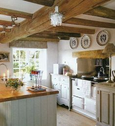 Beautiful European country kitchen with rustic wood beamed ceiling and plates hung on wall.