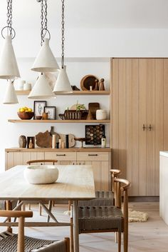 White oak kitchen with oak dining room table and floating shelves