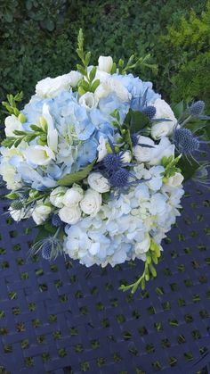 Light blue hydrangea, blue thistle and white spray rose bridal bouquet.